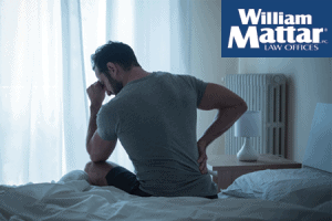 Man Sitting in bed dealing with pain and suffering